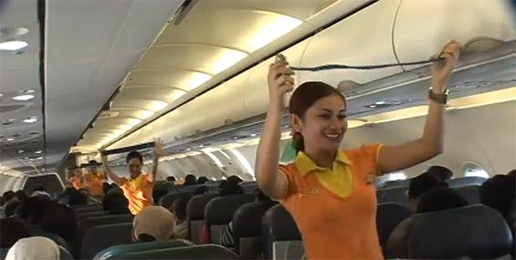Згодни стјуардеси танцувајќи ги демонстрираат безбедносните мерки