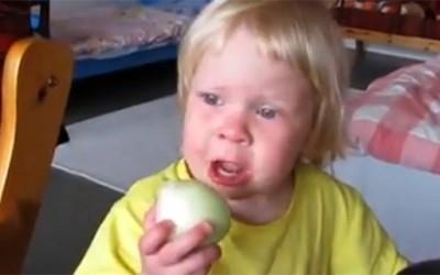Девојче ужива јадејќи главица кромид