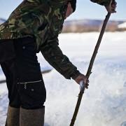 Локален жител го поминува своето време обидувајќи се да улови риба од под мразот.