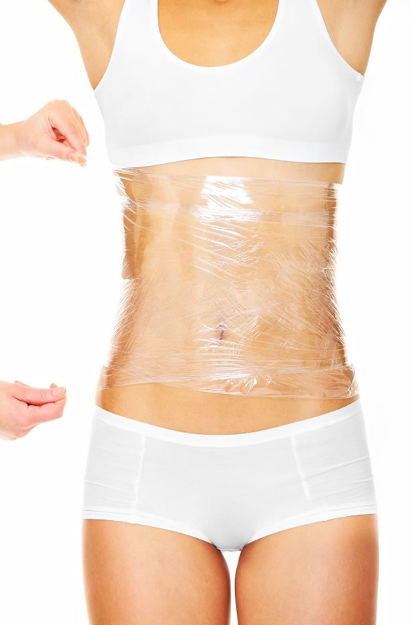 A picture of a sexy female body being wrapped around with foil to reduce fat over white background