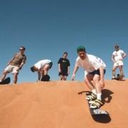 Спуштајте се со даска низ песочните дини во Арабија