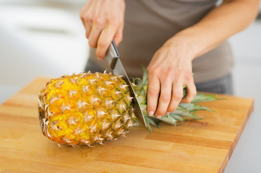 Closeup on woman cutting pineapple