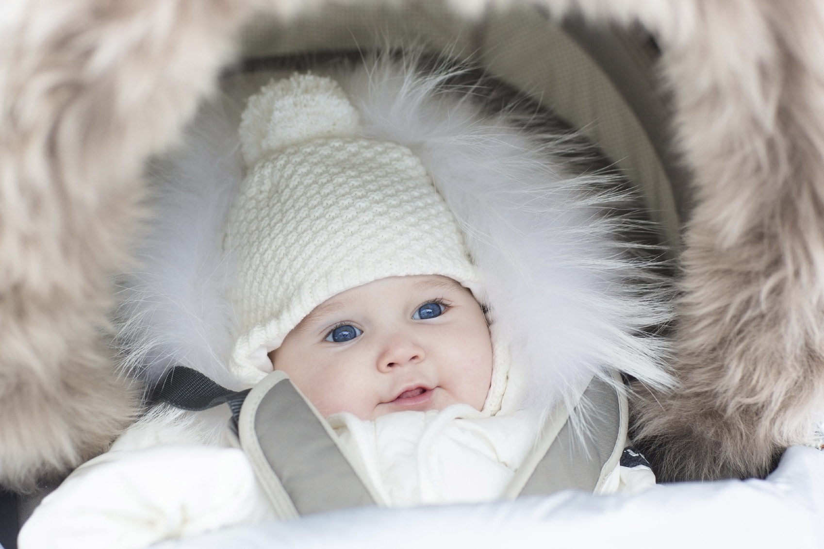 Adorable smiling little baby sitting in a warm stroller on a wal